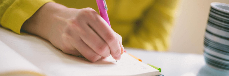 Hand mit Stift, die in ein Notizbuch schreibt