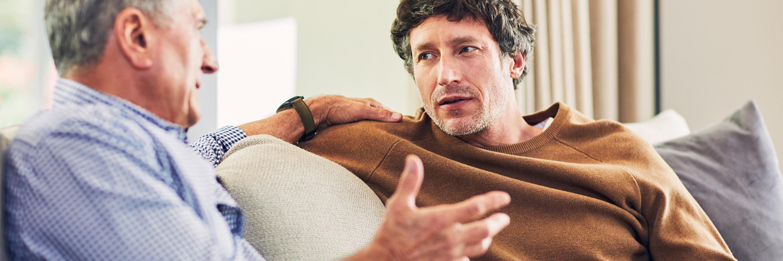 Älterer Mann redet mit jüngerem Mann auf der Couch