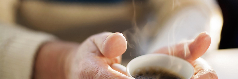 Frauenhände umschließen Kaffeetasse