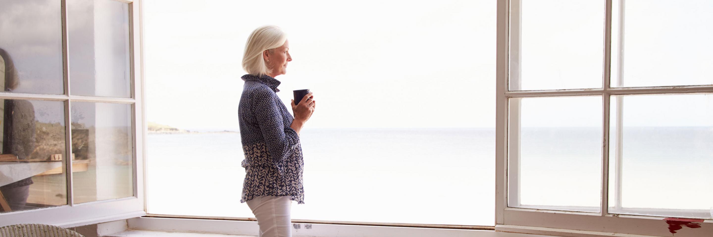 Frau am offenen Fenster mit Blick aufs Meer