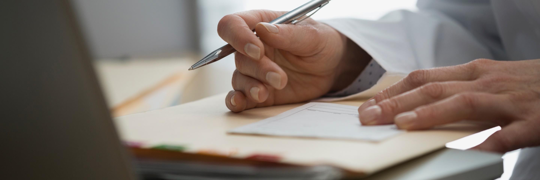 Arzthand beim Unterschreiben eines Attests