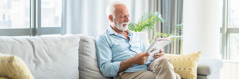 Älterer Mann auf Sofa mit Zeitschrift