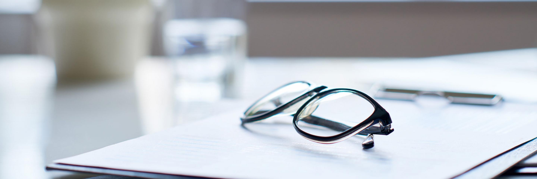 Tisch mit Akten und einer Brille