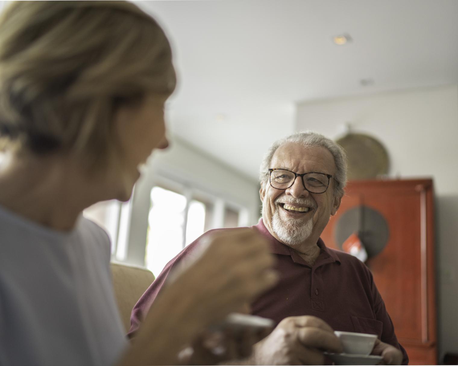 Lachender älterer Herr im Gespräch mit einer Frau