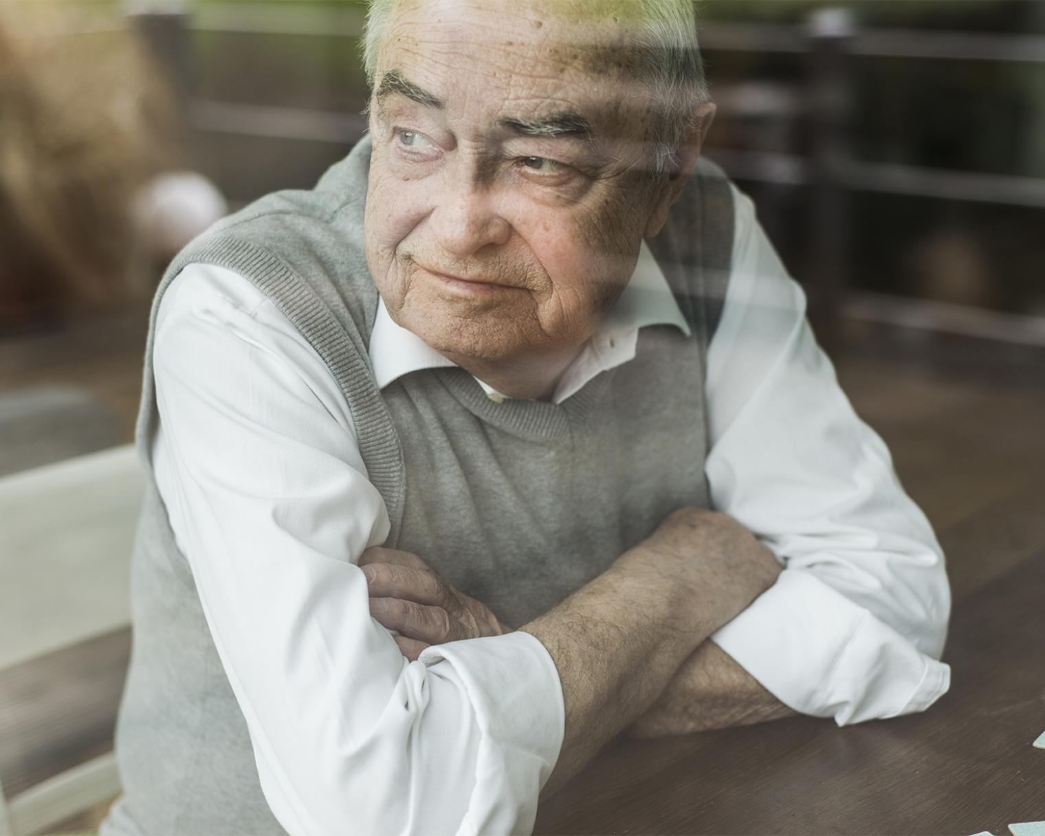 Senior blickt durch ein Fenster