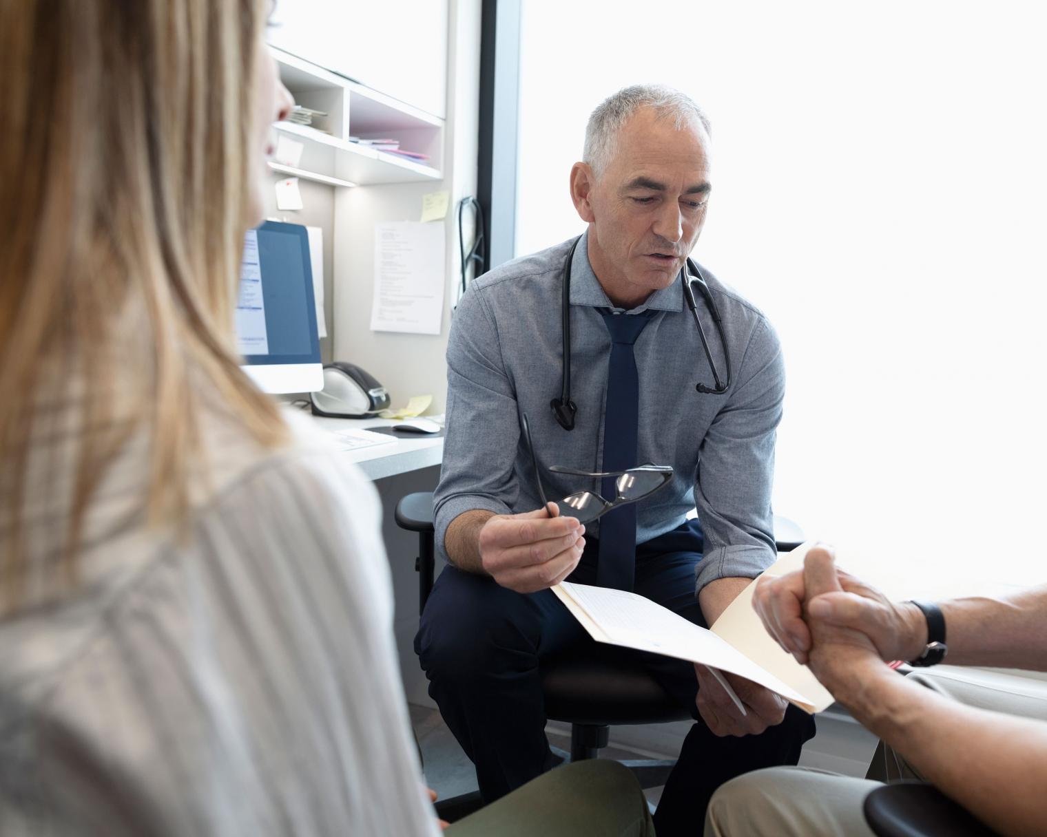 Arzt bespricht mit Patient und Begleitung die Diagnose