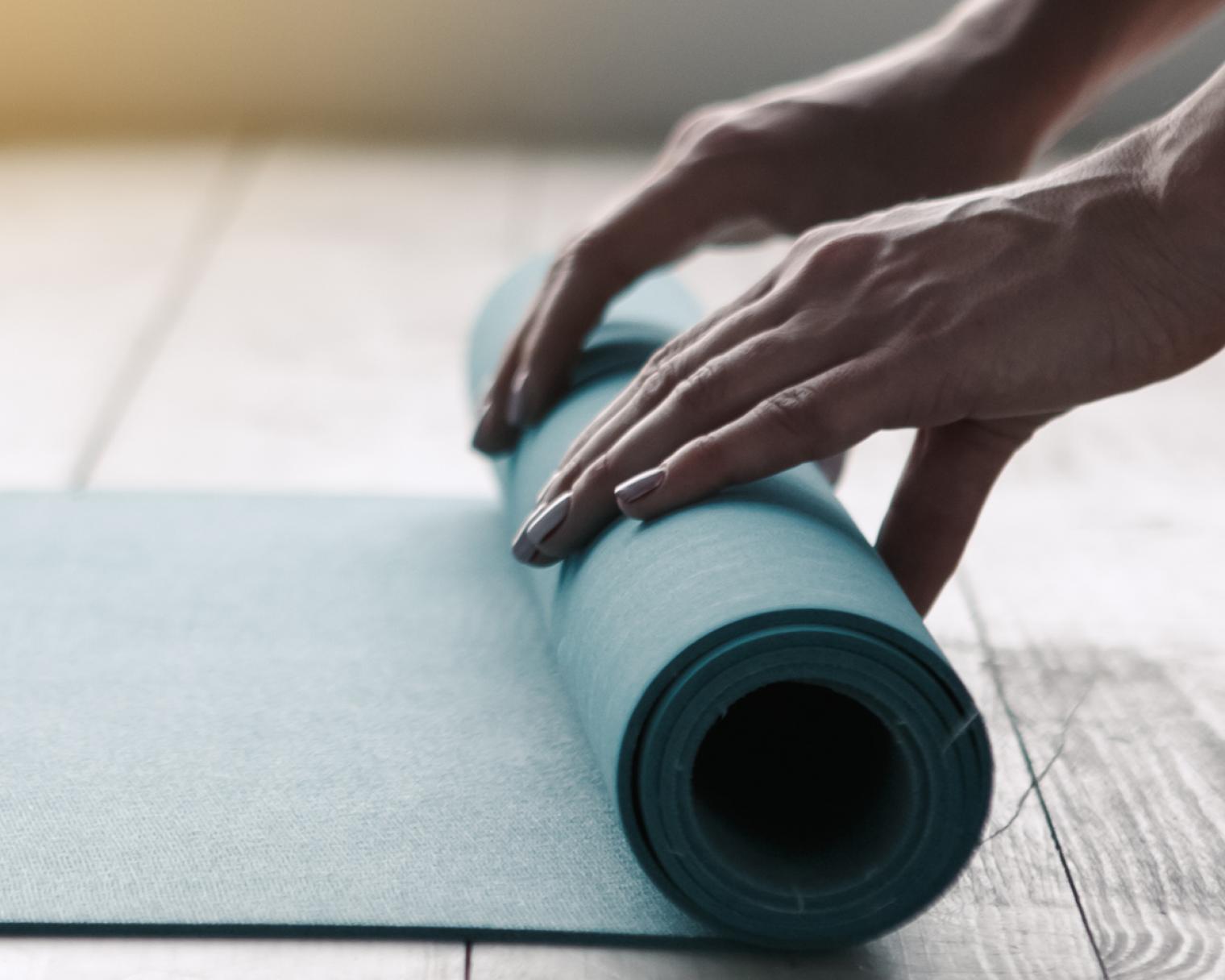 Hände, die eine Yogamatte ausrollen