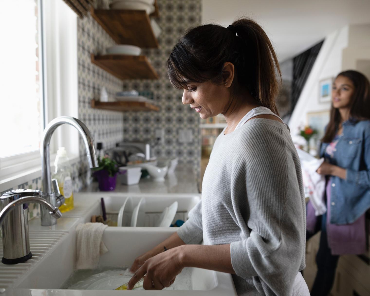 Frau mit Tochter beim Abspülen