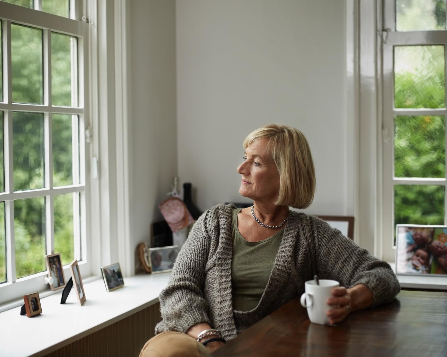 Frau sieht nachdenklich aus Fenster