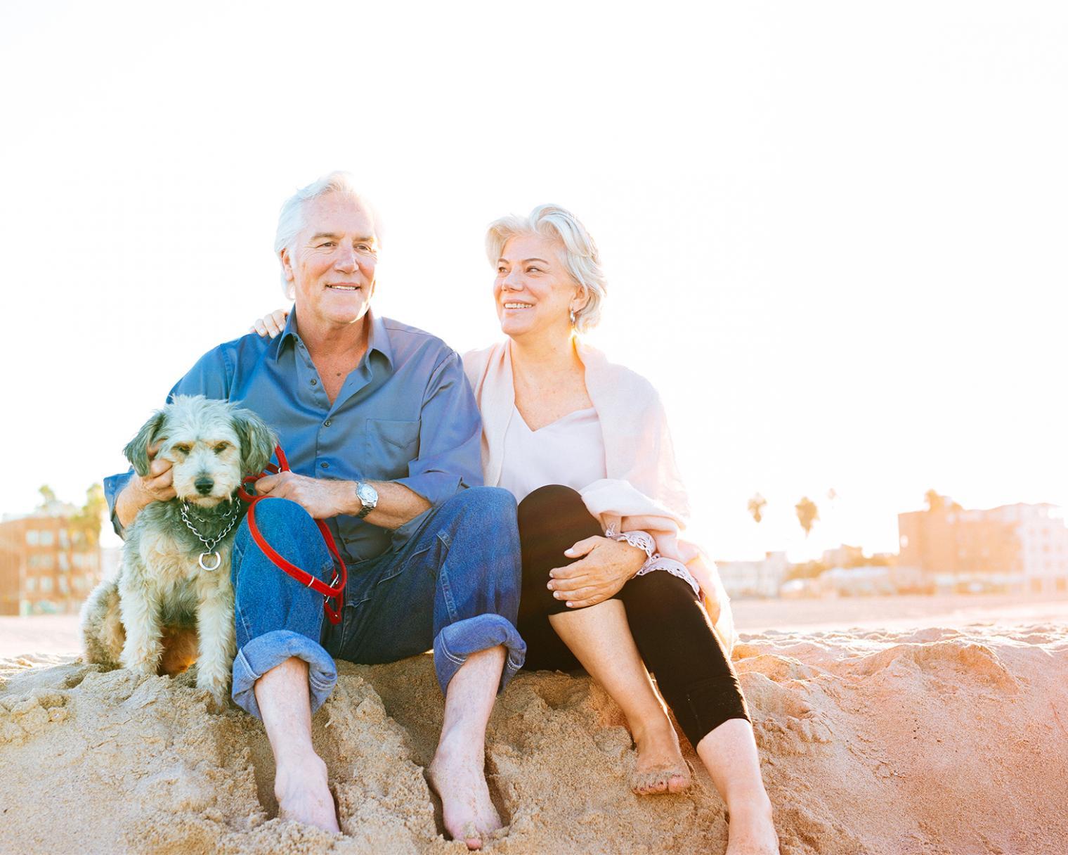 Aktives Paar mit Hund am Strand