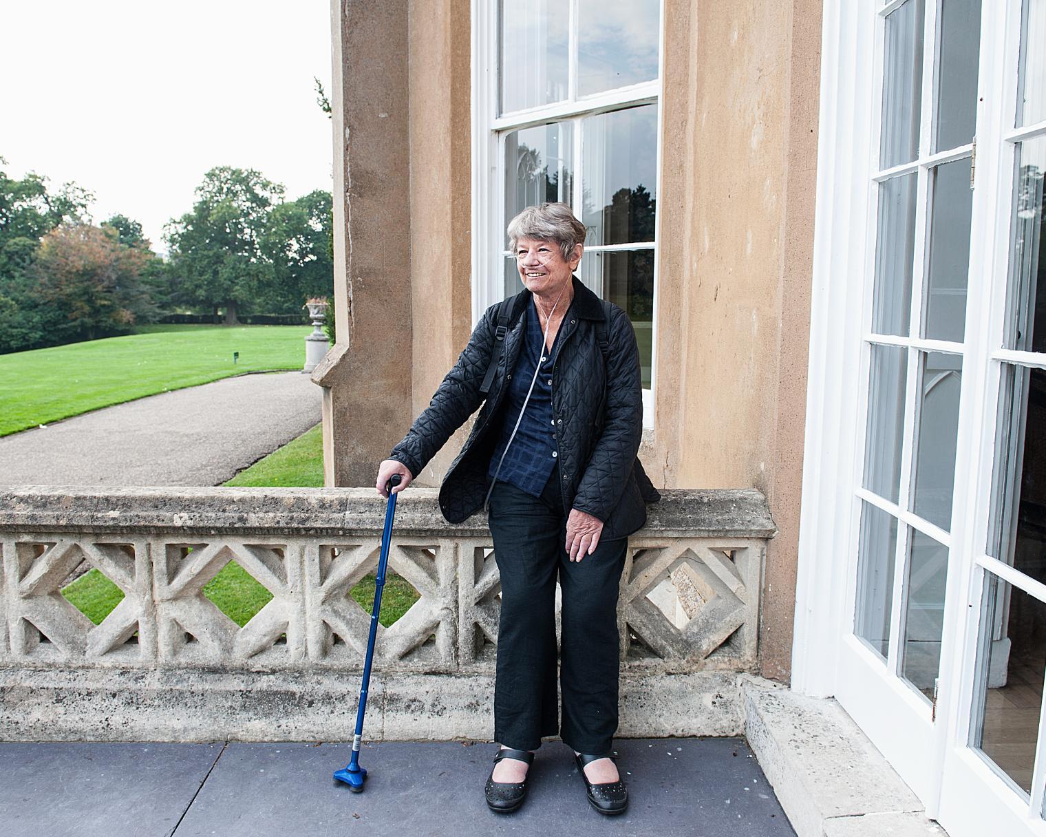 Frau mit Sauerstoffgerät vor Haus