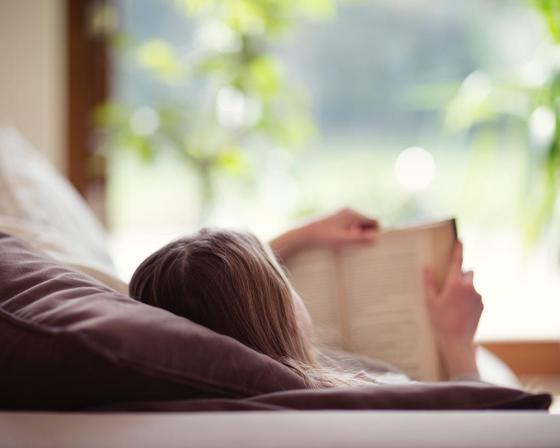 Woman reading a book and laying down