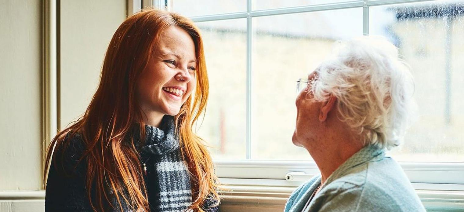 Grandmother and granddaughter smiling together by a window