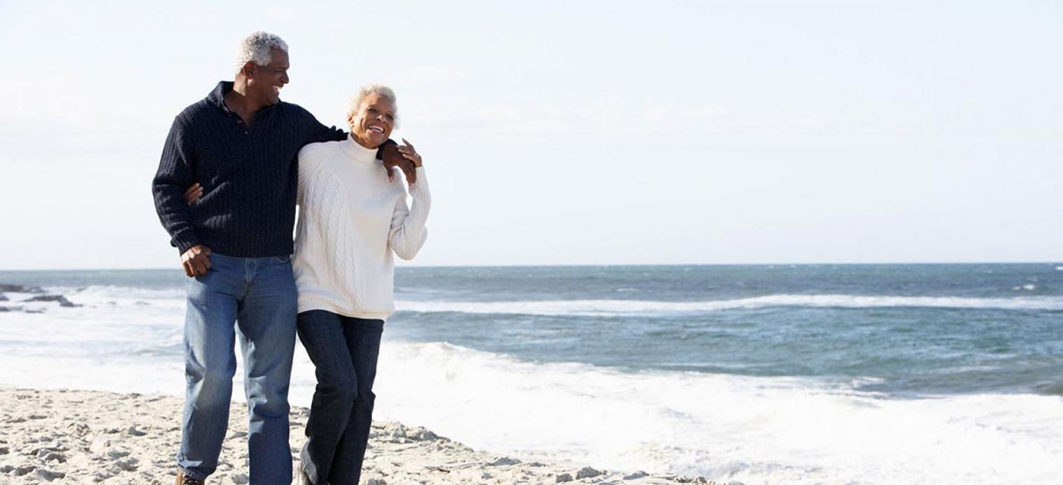 Elderly couple strolling along beach laughing together