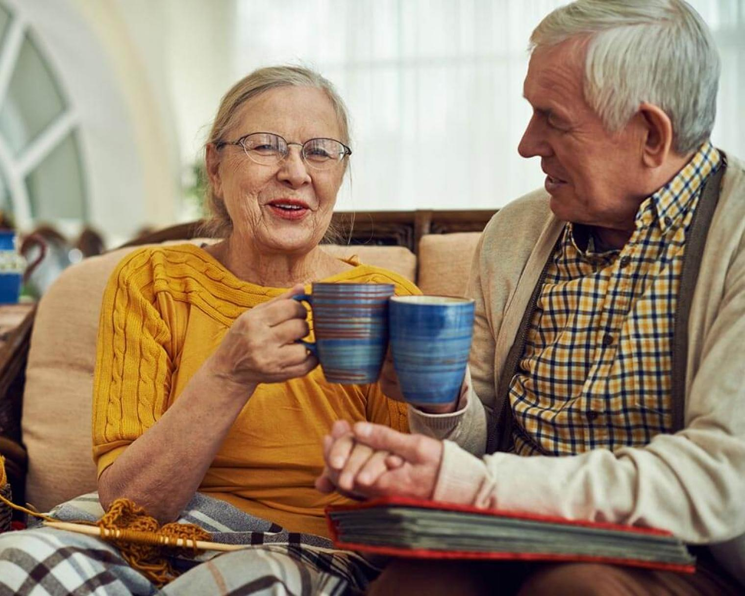Elderly couple sitting together drinking hot drink