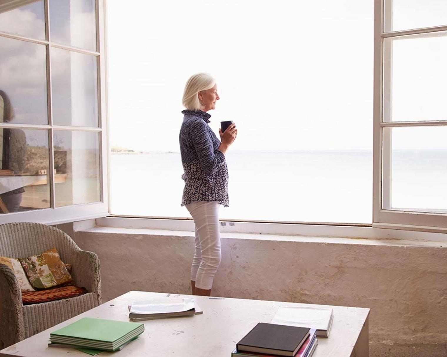 Woman standing in front of large, open window looking at the sea