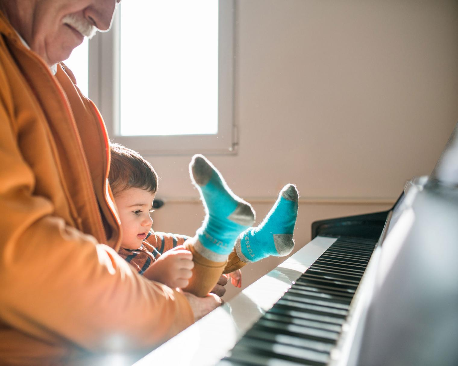 Grandfather and toddler sitting at a piano