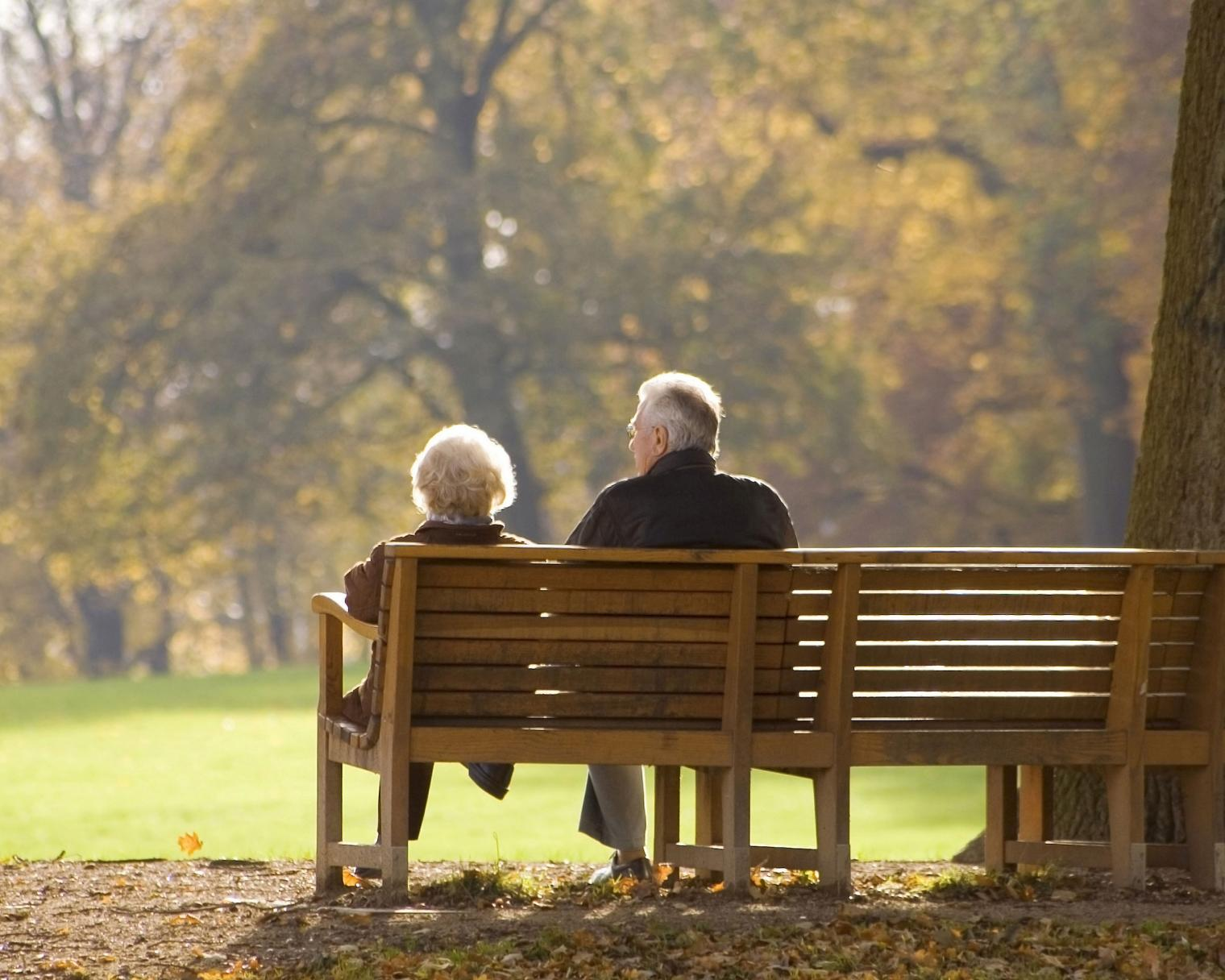 Elderly couple sitting together on a bench in a park